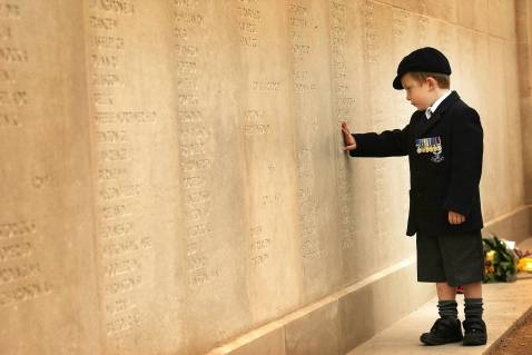 LICHFIELD, UNITED KINGDOM - OCTOBER 12: Five-year-old Alex Wall, of Norfolk, proudly wears his fathers medals as he searches for his father's name on the wall of the Armed Forces Memorial on 12 October, 2007, Lichfield, England.