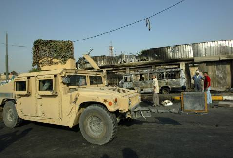 A US Humvee drives past the site of a car bomb explosion in northern Baghdad, 14 October 2007.