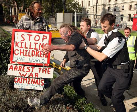LONDON - OCTOBER 19: Police forcibly remove a peace protestor from an empty statue plinth in Parliament Square on October 19, 2007 in London, England.