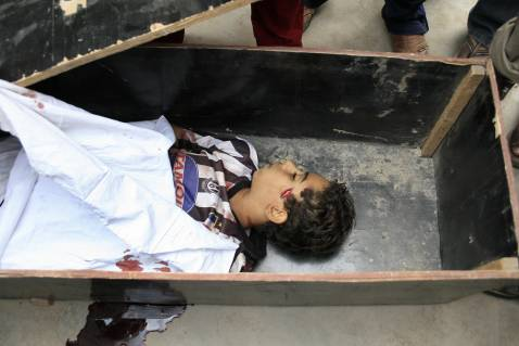 The body of an Iraqi boy killed during fights between US troops and militants in Baghdad's Sadr City neighborhood lies in a coffin, 21 October 2007.