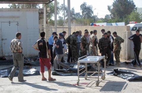 Iraqis gather near bodies at a morgue in Baquba, 50 kms northeast of Baghdad, following a bomb attack 29 October 2007.