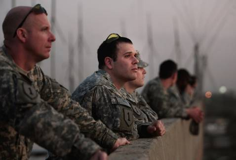 BAGHDAD, IRAQ - NOVEMBER 05: U.S. Army Capt. Nick Kron of Richmond, Virginia (C) and other soldiers in Task Force Justice watch the sunset over the Khadimiyah mosque before an awards ceremony November 5, 2007 in Baghdad, Iraq.