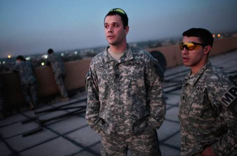 BAGHDAD, IRAQ - NOVEMBER 05: U.S. Army Capt. Nick Kron of Richmond, Virginia (L) and First Sgt. Antonio Gonzales (R) of Brooklyn, New York, both of Task Force Justice, watch the sunset over the Khadimiyah mosque before an awards ceremony November 5, 2007