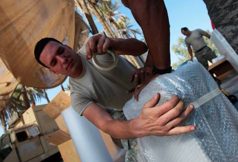 BAGHDAD, IRAQ - NOVEMBER 05: Sgt. John Ivanov of Brooklyn, New York covers equipment with padding for Task Force Justice before loading it to leave November 5, 2007 in Forward Operating Base Justice in Baghdad, Iraq.
