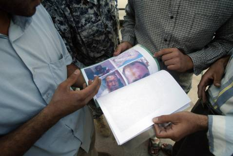 Iraqis inspect a booklet distributed by the police in the holy city of Karbala, 10 November 2007, showing victims allegedly killed by Shiite militiamen affiliated to the Mahdi Army.