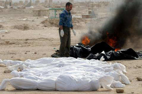 An Iraqi worker burns clothes in a cemetery for unidentified bodies in the Shiite holy city of Najaf, central Iraq, 16 November 2007.