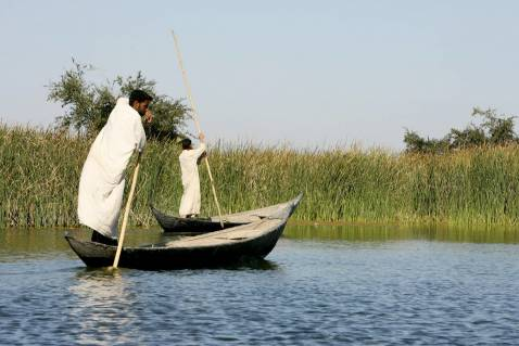 Iraqis ride their canoes in the waters of the marshes area near the southern city of Nasiriyah, 25 November 2007.