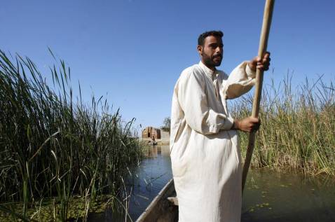 An Iraqi man rides a canoe in the waters of the marshes area near the southern city of Nasiriyah, 25 November 2007.