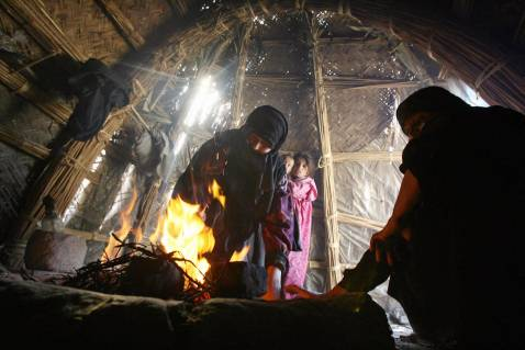 An Iraqi woman lights a fire inside her hut in the marshes area near the southern city of Nasiriyah, 25 November 2007.