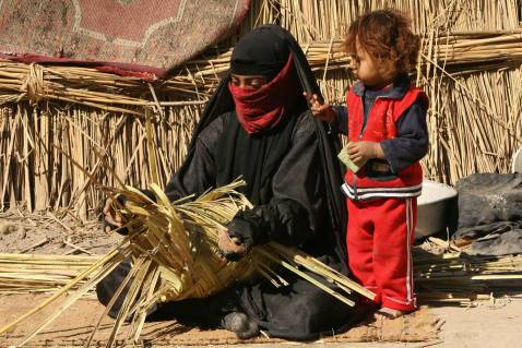 An Iraqi woman makes a basket out of reed as she sits outside her hut in the marshes area near the southern city of Nasiriyah, 25 November 2007.