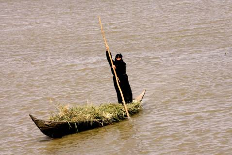 An Iraqi woman rides a canoe in the waters of the marshes area near the southern city of Nasiriyah, 25 November 2007.