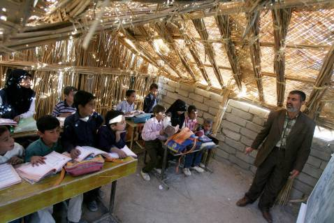 An Iraqi teacher lectures a class at a reed-roofed school in the marshes area near the southern city of Nasiriyah, 25 November 2007.