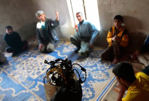 DIYALA PROVINCE, IRAQ - DECEMBER 03: A U.S. soldier in the 4th Stryker Brigade, 2nd Infantry out of Ft. Lewis, Washington, confronts a group of men with a strand of 'crush wire' attached to a blasting cap used for roadside bombs found in the house.