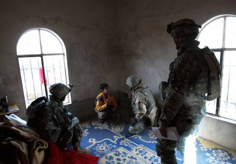 DIYALA PROVINCE, IRAQ - DECEMBER 03: U.S. soldiers and a translator in the 4th Stryker Brigade, 2nd Infantry out of Ft. Lewis, Washington separate a 12-year-old boy from other men in a house for questioning December 3, 2007 in Mukhisa, Iraq.