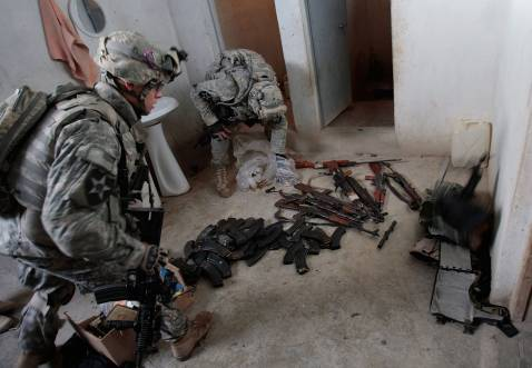 DIYALA PROVINCE, IRAQ - DECEMBER 03: U.S. soldiers in the 4th Stryker Brigade, 2nd Infantry out of Ft. Lewis, Washington, look over a large array of assault rifles and ammunition found in a home December 3, 2007 in Mukhisa, Iraq.