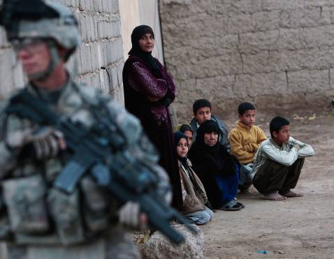 DIYALA PROVINCE, IRAQ - DECEMBER 03: A U.S. soldier with the 4th Stryker Brigade, 2nd Infantry out of Ft. Lewis, Washington stands guard next to women and children during a house during a search December 3, 2007 in Mukhisa, Iraq.