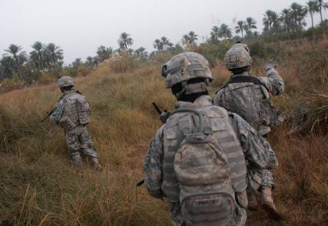 DIYALA PROVINCE, IRAQ - DECEMBER 03: U.S. soldiers with the 4th Stryker Brigade, 2nd Infantry out of Ft. Lewis, Washington, traverse fields on the way to conducting house to house searches December 3, 2007 in Mukhisa, Iraq.