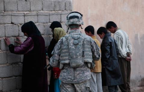 DIYALA PROVINCE, IRAQ - DECEMBER 03: A U.S. soldier with the 4th Stryker Brigade, 2nd Infantry out of Ft. Lewis, Washington, stands guard over women and children in a house during a search December 3, 2007 in Mukhisa, Iraq. The search turned up nothing and the troops went on their way.
