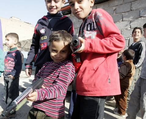 Children play with toy guns on the second day of the Eid al-Adha festivities in the al-Khullani neighbourood, central Baghdad, 20 December 2007.