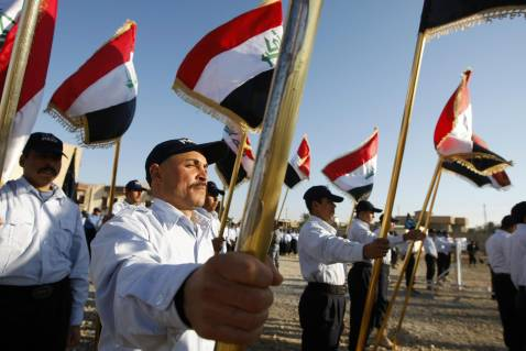 Iraqi recruits hold their nationa flag as during a graduation ceremony for more than 945 Iraqi Police (IP) students, including three women, from the Sons of Iraq Sunni militia at the Al-Furat Iraqi Police training centre in southern Baghdad on January 14,