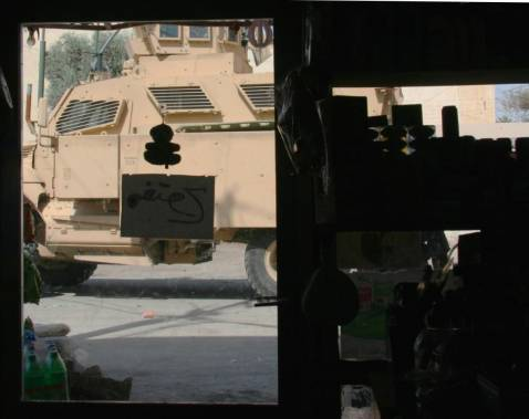 A US Patrol Drives Past a Small Baghdad Shop