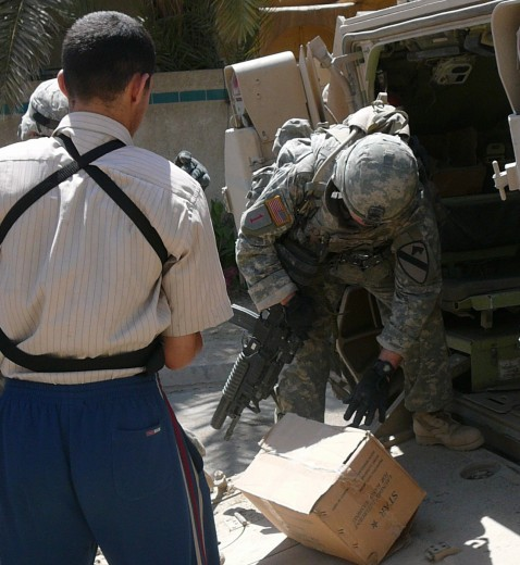 U.S. soldiers hand food to Iraqi resistance fighter in Amiriyah neighborhood of Baghdad.