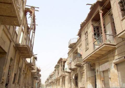 Upper-floor balconies, a traditional feature of Bagdadi residential architecture, are visible in this photo of neglected historic homes.