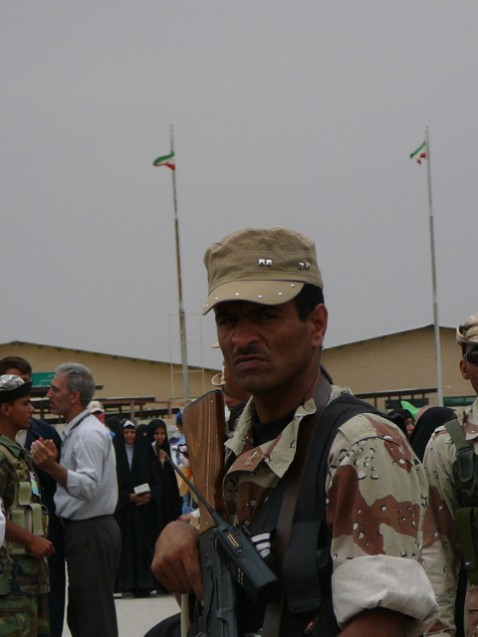 Iraqi soldier flanked by Iranian flags in background at border crossing