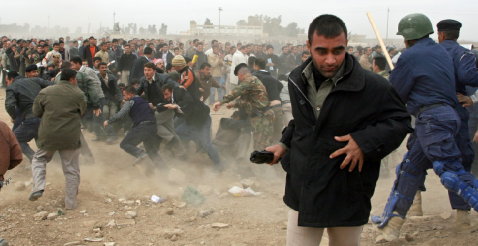 A man runs away as police officers in Kirkuk rush into a crowd of men  who were waiting to apply for jobs as police officers Thursday, Dec. 6, 2007 in Kirkuk.