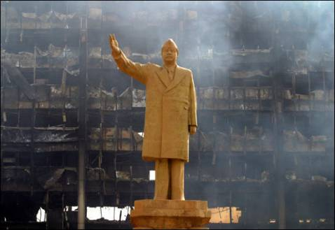 A statue of Saddam Hussein gestures grandly before a burned-out building.