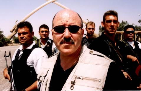 Kerik poses with his South African security detail beneath Saddam Hussein's fabled swords, Aug. 2003.