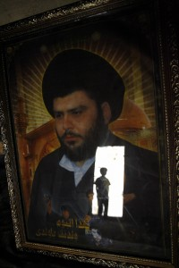 Baghdad, IRAQ: An Iraqi boy is reflected on the glass of a framed picture of Shiite firebrand cleric Moqtada al-Sadr.
