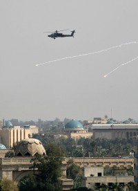 A US Army Apache helicopter drops flares as hovers over the fortified green zone in Baghdad, on April 12, 2007, after a bomb killed a Iraqi MP inside the Parliament cafeteria.