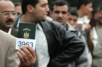 An Iraqi refugee shows his passport as he waits in queue to register at the UNHCR center in the Damascus suburb of Duma, April 23  2007.