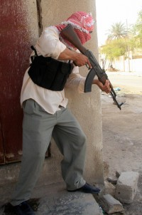 Basra, IRAQ: An armed man waits behind a building during brief clashes after gunmen ambushed a British military supply convoy in the Iraqi southern city of Basra, 21 May 2007.