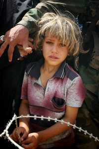An Iraqi boy waits as Iraqis rush to receive humanitarian aid from the Iraqi Ministry of Trade in Baquba, 60 kms (35 miles) north of Baghdad, 05 August 2007.