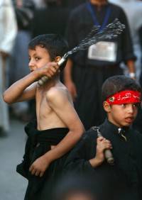 An Iraqi Shiite Muslim boy flagellates himself as part of a major religious festival in the Kadhimiyah district of Baghdad, 08 August 2007.