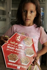 An Iraqi girl shows a box of dates at a shop in Baghdad, 15 August 2007. The world famous Iraqi dates are picked during the months of August and September from orchards made up of some 150 trees. Each tree produces an average of 5 bunches of dates, with e