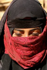 An Iraqi veiled woman sits outside her hut in the marshes area near the southern city of Nasiriyah, 25 November 2007.