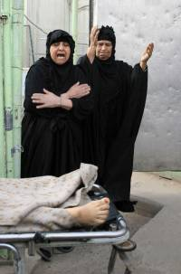 Iraqi women beat their chests in mourning over the death of a relative outside a hospital mortuary in Baghdad's Sadr City on Thursday.