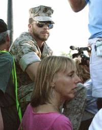 Adam Kokesh of IVAW and Medea Benjamin of CodePink watch as those preparing to cross the police barricades line up.