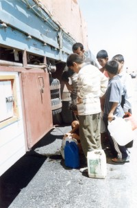 Iraq children fill jugs from a water truck.